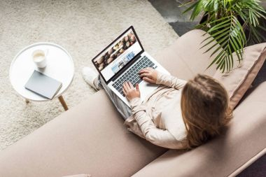 high angle view of woman at home sitting on couch and using laptop with shutterstock homepage on screen