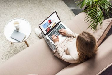 high angle view of woman at home sitting on couch and using laptop with ebay website on screen
