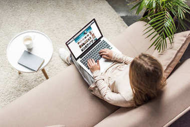 high angle view of woman at home sitting on couch and using laptop with amazon website on screen