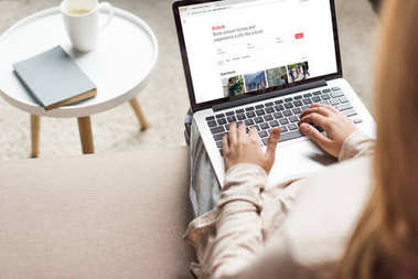 cropped shot of woman at home sitting on couch and using laptop with airbnb website on screen