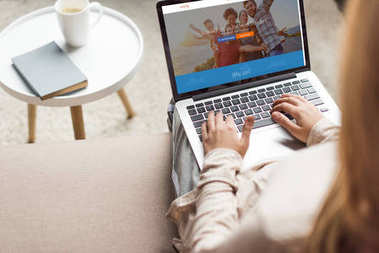 cropped shot of woman at home sitting on couch and using laptop with couchsurfing website homepage on screen