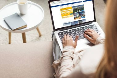 cropped shot of woman at home sitting on couch and using laptop with booking website on screen