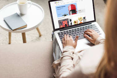 cropped shot of woman at home sitting on couch and using laptop with ebay website on screen