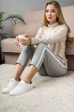beautiful young woman with cup of hot drink sitting on floor at home