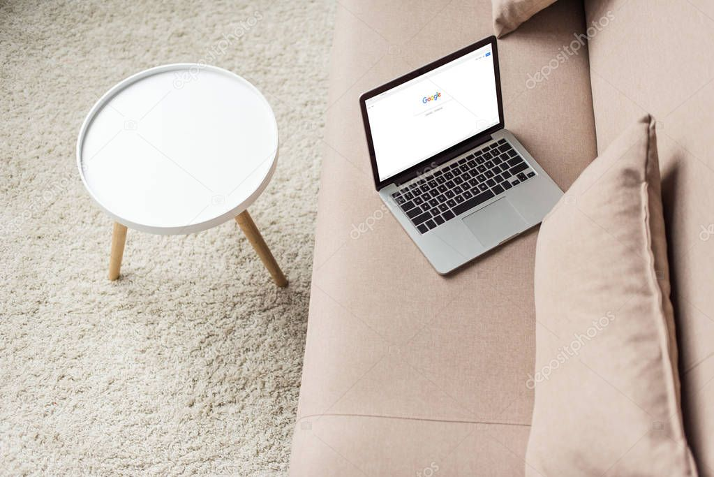 high angle view of laptop standing on cozy couch with google website on screen