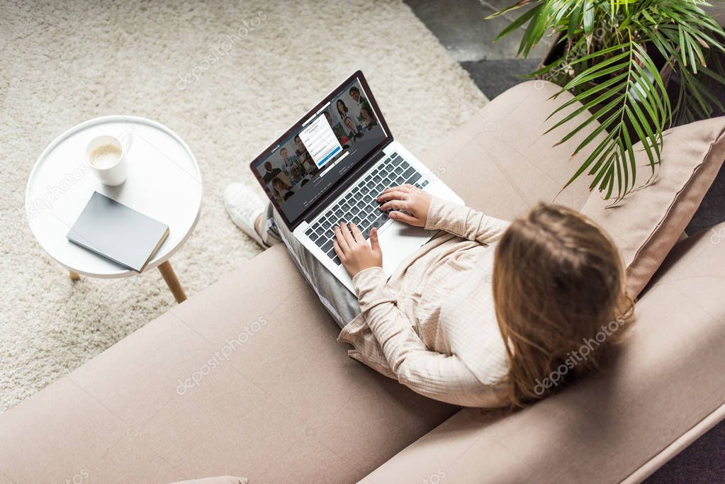 high angle view of woman at home sitting on couch and using laptop with linkedin website on screen