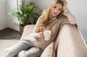 vonzó fiatal nő ül a kanapén, forró itallal csésze