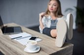 Photo young businesswoman relaxing at workplace with feet on table