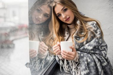 beautiful young woman drinking coffee while leaning on window
