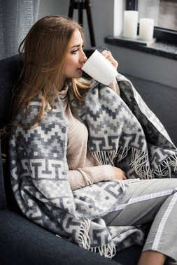 attractive young woman drinking coffee in comfy armchair with wool plaid