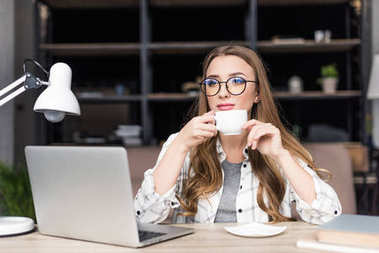 thoughtful young businesswoman drinking coffee at workplace
