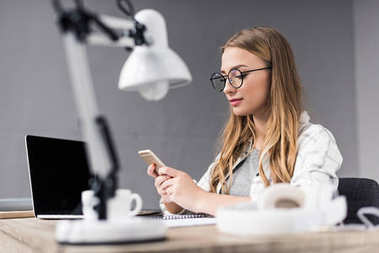 attractive young businesswoman using smartphone at workplace