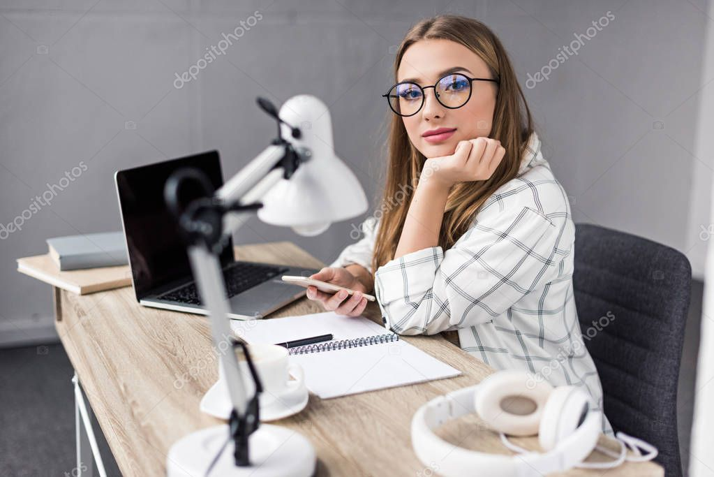 young woman using smartphone at workplace and looking at camera