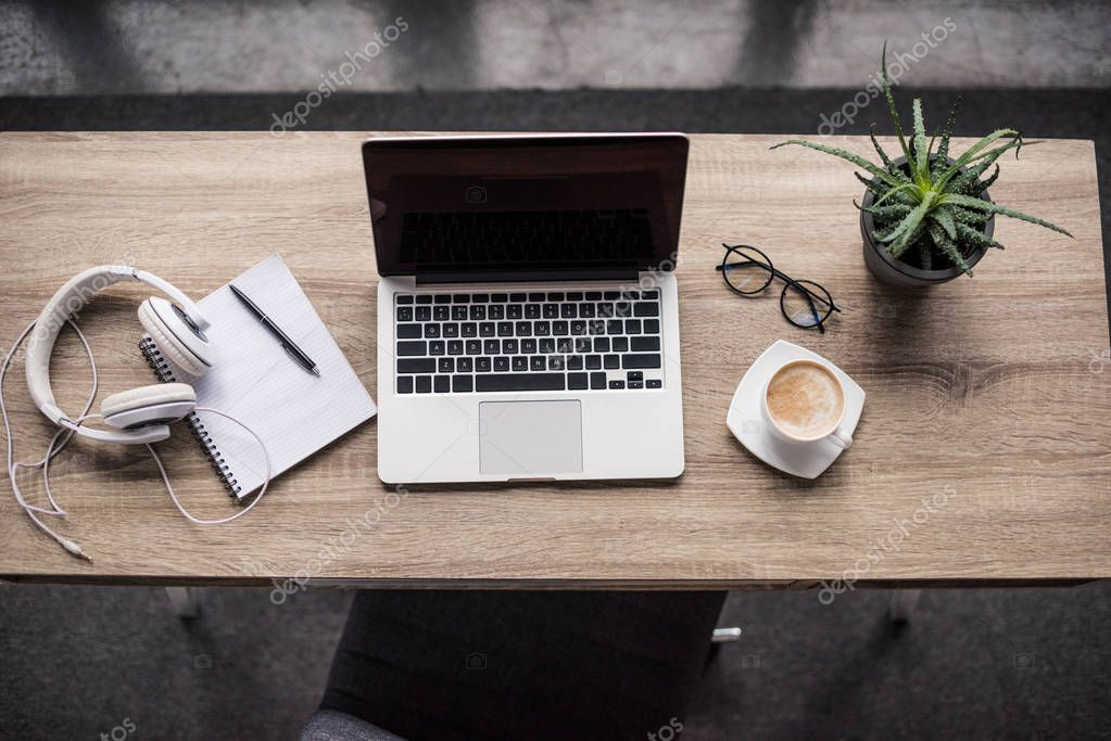 top view of laptop with cup of coffee and headphones at modern workplace