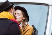 Fotografie beautiful young couple kissing beside car