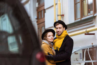 young attractive couple hugging behind car