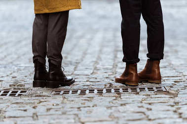 cropped image of female and male legs in autumn shoes