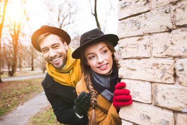 cheerful young couple in autumn outfit looking at corner