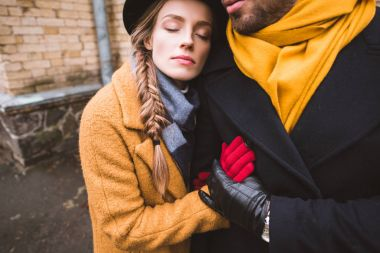 cropped image of beautiful hugging couple in autumn outfit