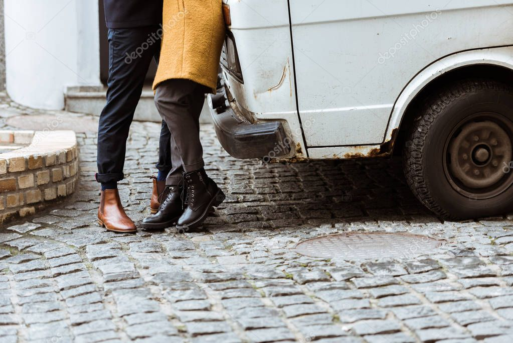 cropped image of couple in autumn outfit hugging beside car