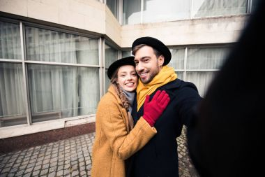 happy hugging young couple taking selfie infront of building