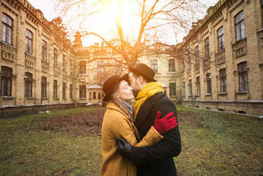 cheerful attractive young couple hugging infront of building