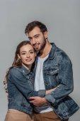 szép boldog fiatal pár átölelve hoznak, és mosolyogva kamera elszigetelt szürke