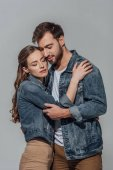 beautiful happy young couple with closed eyes hugging isolated on grey