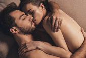 Fotografie sensual naked young couple hugging and sleeping together in bed