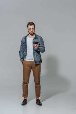 full length view of handsome sylish young man in eyeglasses using smartphone isolated on grey