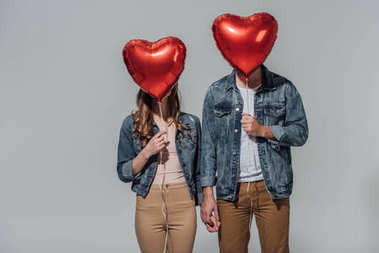 young couple hiding faces behind red heart shaped balloons isolated on grey