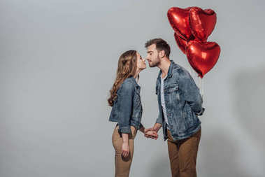 side view of young couple able to kiss while man holding red heart shaped balloons isolated on grey