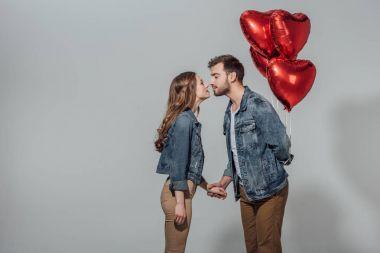 Genç çift gri izole kırmızı kalp şeklinde balonlar tutan adam öpmeye mümkün yan görünüm