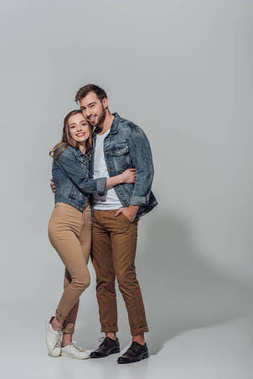 full length view of cheerful young couple hugging and smiling at camera isolated on grey