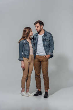 Full length view of smiling young couple in denim jackets looking at each other isolated on grey stock vector