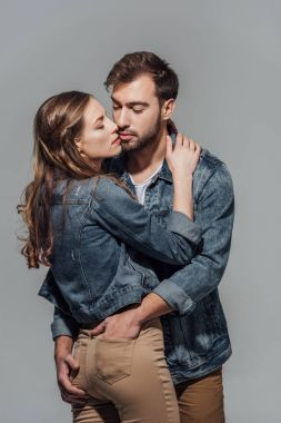 seductive young couple in denim jackets hugging isolated on grey