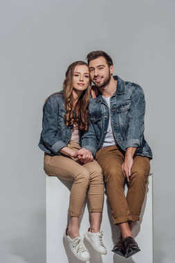 Beautiful young couple in denim jackets sitting together and smiling at camera isolated on grey stock vector