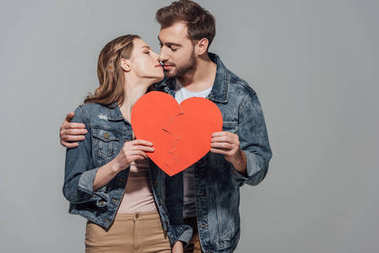 young couple holding pieces of broken heart symbol together and kissing isolated on grey