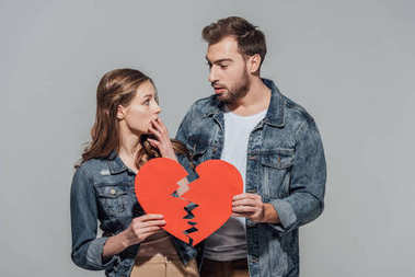 upset young couple holding pieces of broken heart symbol isolated on grey