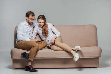 happy young couple using smartphone together while sitting on sofa isolated on grey