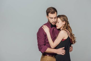 beautiful stylish young couple on love embracing isolated on grey