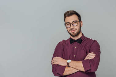 stylish young man in eyeglasses standing with crossed arms and smiling at camera isolated on grey