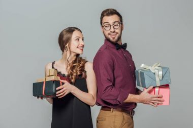 happy stylish young couple holding gift boxes and smiling each other isolated on grey