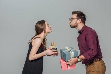 mutlu genç çift hediye kutuları tutarak ve öpmek için gri izole yan görünüm