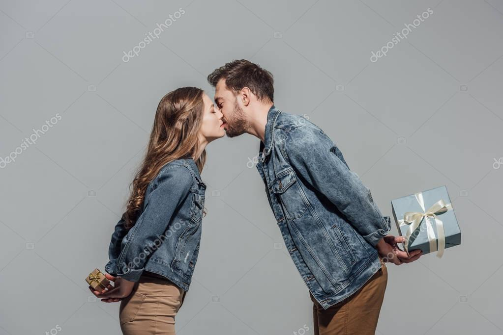 side view of beautiful young couple in love holding gift boxes and kissing isolated on grey