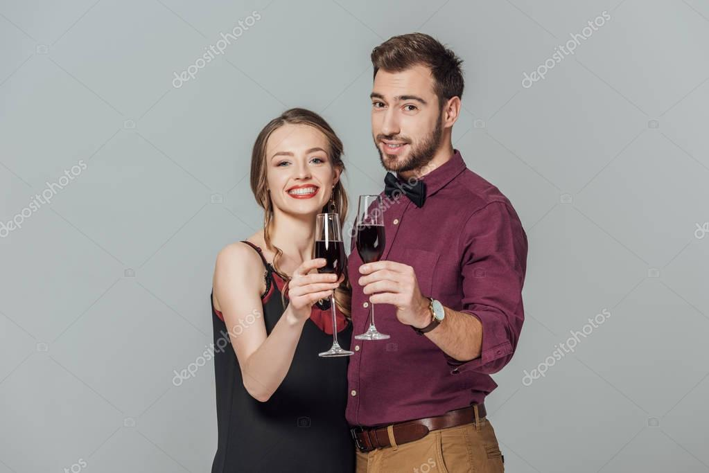 beautiful elegant young couple holding glasses of red wine and smiling at camera isolated on grey