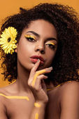 Photo Young sensual african american woman with artistic make-up and gerbera in hair holding finger on lips isolated on orange background