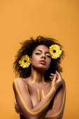 Young african american woman with artistic make-up and gerbera in hair standing with crossed arms isolated on orange background