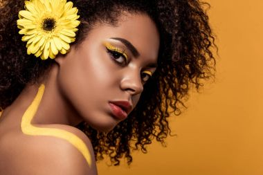 Young tender african american woman with artistic make-up and gerbera in hair looking at camera isolated on orange background