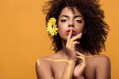 Young sensual african american woman with artistic make-up and gerbera in hair holding finger on lips isolated on orange background